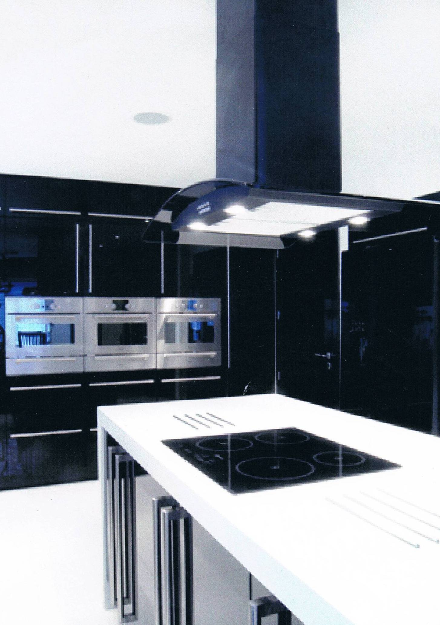 Black gloss doors with glacier white corian worktops and end panels with a corian sink