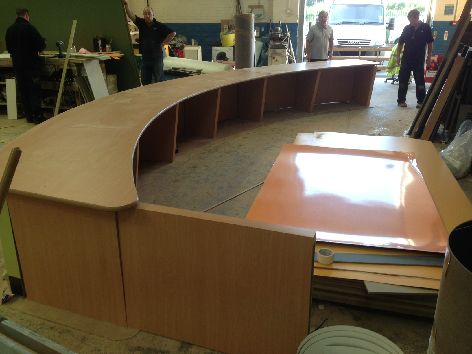 University reception counter - Liverpool . Top manufactured from 25 mm Mdf and  laminated with formica laminate with clear lacquered edges front of counter made from flexi ply and   mdf and laminated in green fomica .